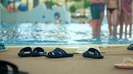 пляжная одежда : Many slippers on the shore of an indoor aqua park. Defocused background