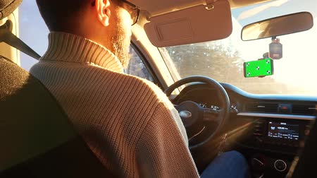 girandola : A man driving a car in the winter on a sunny highway. Smartphone has a green screen attached to the windshield. Filmati Stock