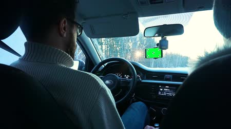 csatolt : A man driving a car in the winter. Smartphone has a green screen attached to the windshield.