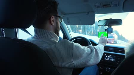 csatolt : A man driving a car in the winter. Smartphone has a green screen attached to the windshield, it presses a finger on the screen.