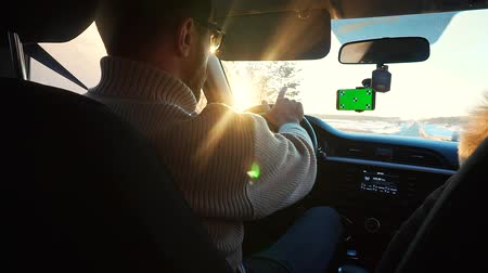 navigasyon : A man driving a car in the winter on a sunny highway. A smartphone has a green screen attached to the windshield, a man shows on the highway ahead. Stok Video
