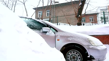 kar taneleri : Timelapse - Man cleaning snow from car with brush in living house district. Stok Video