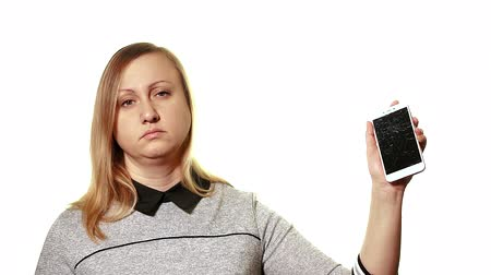 destruído : The concept of a broken gadget. Tired sleepy woman holding a smartphone with a broken screen. Vídeos