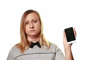 crashed : The concept of a broken gadget. Tired upset woman shows a broken smartphone screen.