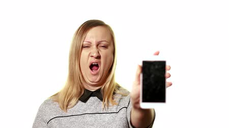 ziewanie : The concept of a broken gadget. Frustrated and tired middle-aged woman holding a smartphone in front of him, his screen is broken. Wideo