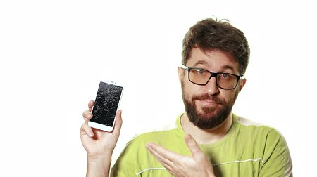 zuřivý : The concept of a broken gadget. Bearded frustrated man shows the smartphone with a broken screen. Dostupné videozáznamy