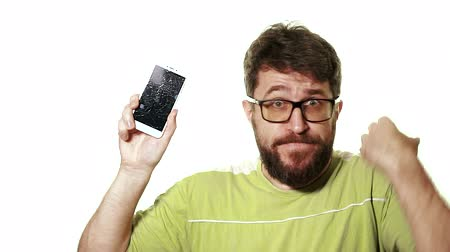 crashed : The concept of a broken gadget. A bearded man shows the smartphone with a broken screen. He curses in despair and is angry.