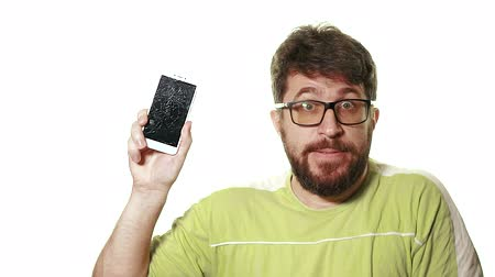 shattered : The concept of a broken gadget. Bearded angry man showing broken smartphone screen. Stock Footage