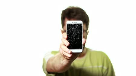 shattered : The concept of a broken gadget. Bearded frustrated man shows the smartphone with a broken screen. Stock Footage
