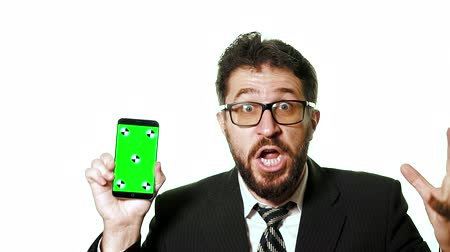 se moquer : A conceptual mockup. Bearded businessman with glasses holding a smartphone with a green screen. Hes on a white background crazy, happy, hes a winner, slow motion