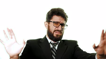 tél : Bearded businessman wearing glasses and a suit on a white background. He is in fear and horror waving his arms, did not want trouble, slow motion