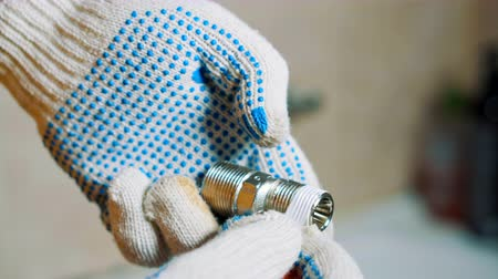 su tesisatı : Close-up gloved hands A man is sealing tape wrap around iron water tap screw. Stok Video