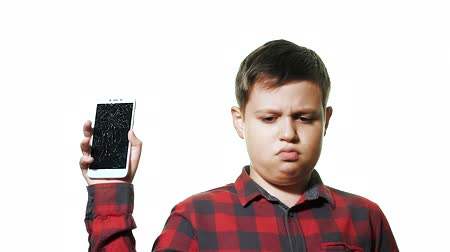 crashed : The concept of a broken gadget. Sad teen boy on white background. Hes holding a smartphone with a broken screen.