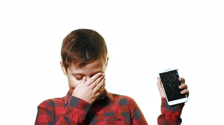 křaplavý : Teen boy is hilarious. Close-up on a white background, it shows a broken smartphone Dostupné videozáznamy