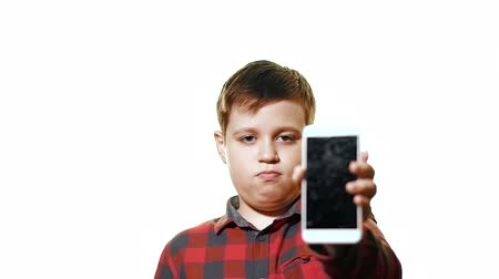 shattered : Teen boy is upset and sad. Close-up on a white background, it looks at the smartphone and shows a broken screen Stock Footage