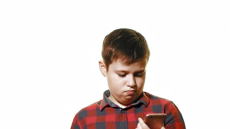 треснувший : Teen boy is upset and sad. Close-up on a white background, he looks at the smartphone that is not working Стоковые видеозаписи