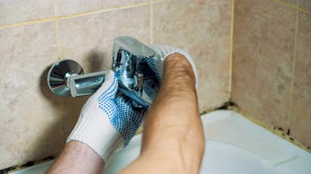 vazamento : Close-up gloved hands of the plumber installs the faucet in the bathroom. Hes tightening the nut.