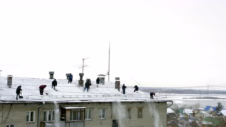 excesso de trabalho : Many men throw white snow from the roof of a multi-storey building. Heavy seasonal male labor. People work as a shovel. They quickly clean the roof of excess snow.