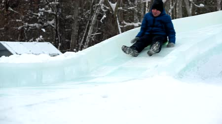 lesiklás : Boy sledging down the hill at winter park. Ice slide in the recreation Park in winter