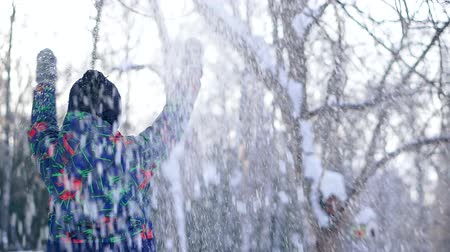 snow angel : Teen boy throws snow in the winter forest. Stock Footage