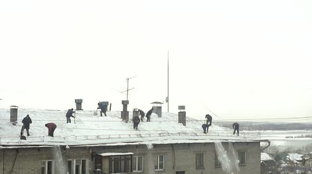 excesso de trabalho : Many men throw white snow from the roof of a multi-storey building. Heavy seasonal male labor. People work as a shovel. They quickly clean the roof of excess snow. Slow motion Vídeos