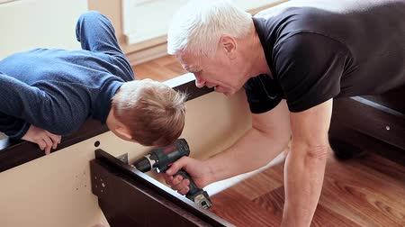 nastavení : Grandfather and grandson are repairing furniture. Grandfather unscrews the screw with an electric screwdriver, disassembles the bed. Grandson looks down.