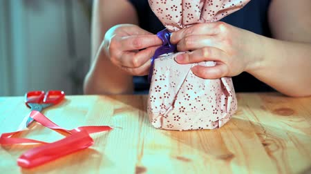 envolto : Close-up of a womans hand packing a gift. Next on the table are a pair of scissors and red packing tape