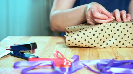 hediyeler : Close-up of womens hands packing a gift. Craft wrapping paper