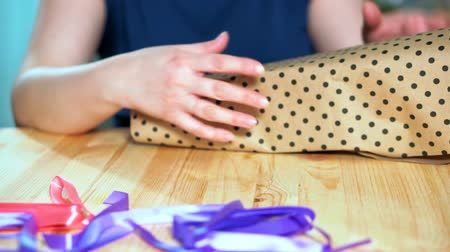 envolto : Close-up of womens hands packing a gift. Craft wrapping paper, on the table lie red and violet packaging Turing