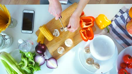 sporák : Top view close-up of a young woman cutting vegetables in the kitchen with a knife on the table. She cuts fresh mushrooms. Next on the table is the smartphone
