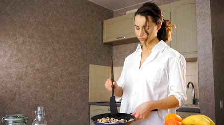 tasting : An attractive young woman in the kitchen. She mixes up the onions and mushrooms to the Pan, then puts the spoon on the table Stock Footage
