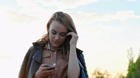 követés : Attractive girl in headphones using smartphone, listening to music and browsing on smartphone. Scrolls through social media on device