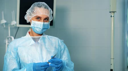зажим : A nurse in the operating room picks up tweezers. She is preparing to give it to the doctor. Стоковые видеозаписи