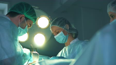 scalpel : Two of surgeons at the work. Nurse gives the doctor medical tweezers Stock Footage