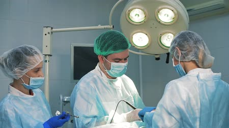 scalpel : Two of surgeons at the work. Male doctor looking at camera
