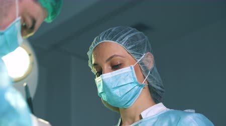 scalpel : Close-up of a female surgeon. She works in the operating room, sweat on her forehead, the nurse wipes the sweat with a swab.