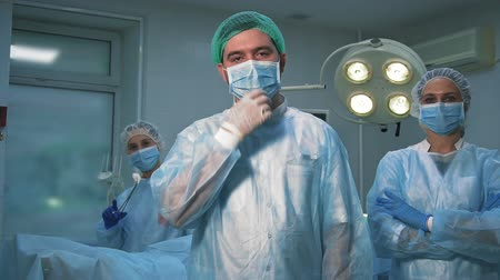 scalpel : The team of surgeons at work in the operating room. Tired but satisfied doctors pose for the camera after surgery.