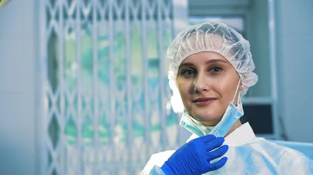 scalpel : Portrait of a surgeon assistant looking at the camera wearing a mask and a bathrobe. She is tired and contentedly smiling, after surgery she removes a surgical mask in slow motion
