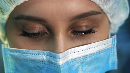 scalpel : Extra close-up of the eyes tired nurse. She is in a mask looking at the camera, after surgery Stock Footage