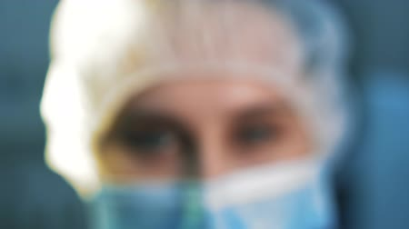 scalpel : Extra close-up of the eyes tired nurse. She is in a mask looking at the camera, after surgery. The camera runs out of defocus