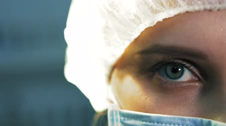 skalpel : Extra close-up of the eye tired nurse. She is in a mask looking at the camera, after surgery