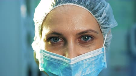 scalpel : Extra close-up of the surgeons eye. She is tired, after surgery, looking into the camera
