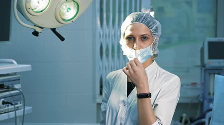especialista : Portrait of a surgeon doctor, after surgery. A tired female surgeon looks into the camera and takes off a surgical mask, she smiles