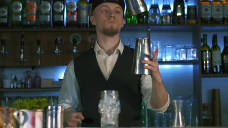 шейкер : Guy-bartender starts his master class of preparation an alcohol cocktail. The process of preparation delicious alcoholic cocktail. Barmen tells on camera in slow motion