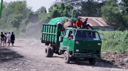 otobüs : Myanmar, Yangon. 21.11.2013  Old truck transporting garbage to the dump. Men ride on the roof of the truck.