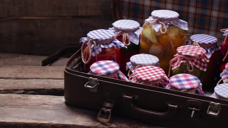enlatamento : Glass jars with preservation in an old suitcase. Wooden shelves of old boards.