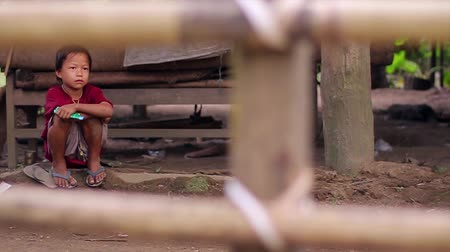 shy girl : Myanmar, Yangon. 12.11.2013  Sad children in the yard. Poor children in the jungle. Hungry children. Stock Footage