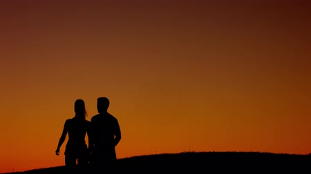 любовь : Loving couple walks of a  beautiful summer evening. Silhouette figures of loving couple. Love story. Walk in the mountains.