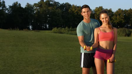 бицепс : Guy and  girl engaged in sports on a golf course. Happy young people involved in sports. Guy train a girl  in the park.