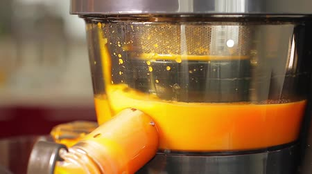 gyümölcslé : Juicer close-up makes fresh orange juice. Preparation of orange juice.